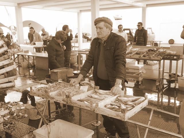 Grumpy man selling fish at Trapani fish market